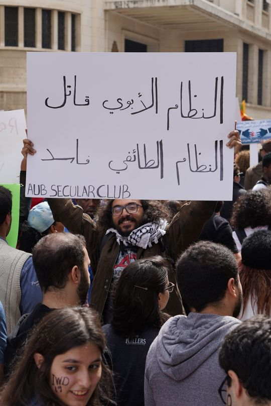 "Man from the AUB Secular Club holding an Arabic sign from the 2019 Women's March in Beirut reads ""The patriarchal system is a killer, the sectarian system is corrupt."" (Laudy Issa)"