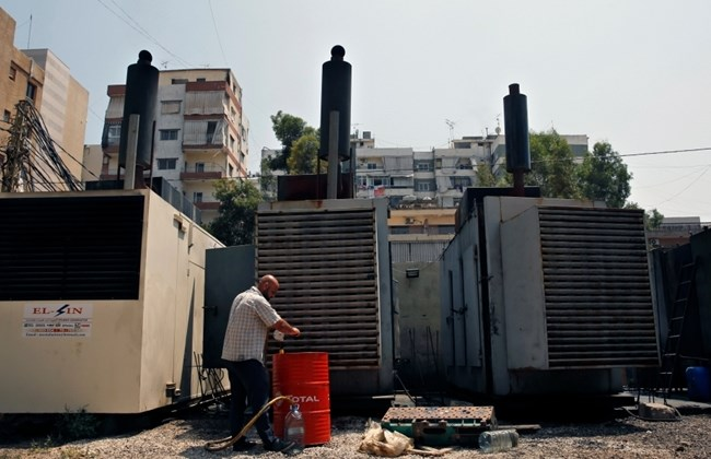 A man stands in front of two private generators in Lebanon.