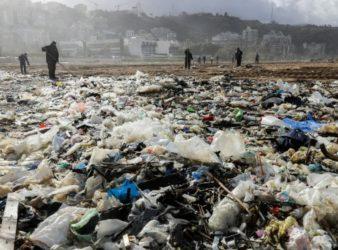 Workers clean the Zouk Mosbeh beach in 2018. (AFP | Joseph Eid)