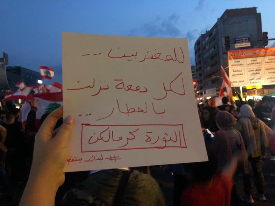 "A sign that reads ""To the expats, to every tear that was shed in the airports, the revolution is for you."""