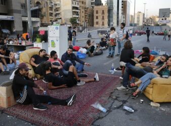 "Demonstrators sit in ""Beit El Cha3eb"" on the Ring highway during a protest in Lebanon. (Hussein Malla/AP)"
