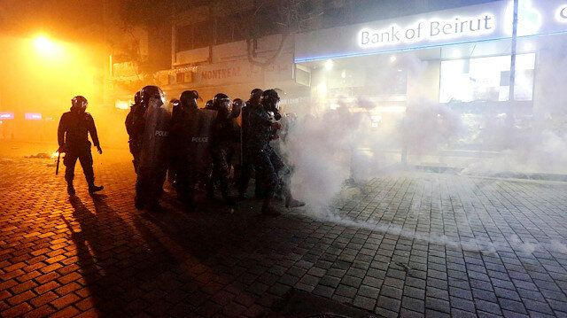 Riot police stand behind riot shields in a cloud of tear gas during protests against the economic crisis outside a Bank of Beirut office in Beirut. January 14, 2020. (PHOTO: Reuters / Mohamed Azakir) / Week of Anger / Protesters and security forces clash