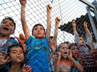 Syrian refugee children chant slogans behind a fence at a refugee camp in Turkey. (Lefteris Pitarakis / AP / The Telegraph)