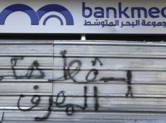 """Down with the rule of the bank"" reads this graffiti on the door of Bankmed, one of the top five banks in Lebanon. A default deals a major blow to the banking system in Lebanon. (AP / Financial Times)"