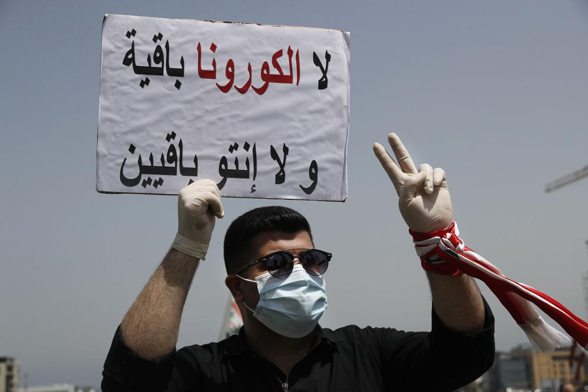 """""""Neither coronavirus nor you will last,"""" reads this sign from a protester in Lebanon on April 24. (Photo: Lebanon Express via Hussein Malla / Ap) Lira plummet article"""