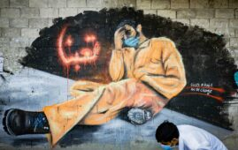 """Man in face mask walks past a mural that reads """"We Are Tired"""" in Tripoli, Lebanon. (Photo: AFP)"""