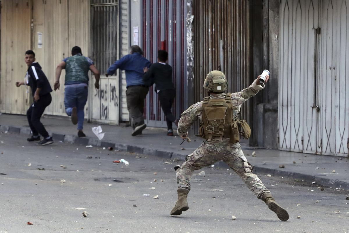 A Lebanese army soldier throws a tear gas canister towards anti-government protesters in Tripoli, Lebanon on Tuesday, April 28, 2020. (PHOTO: Bilal Hussein / AP)
