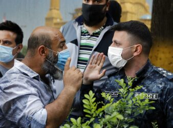 Anti-government protester yells at an Internal Security Forces police officer while demonstrating against Lebanon's worsening economic crisis in the middle of the COVID-19 pandemic. (Photo: Bilal Hussein / AP)