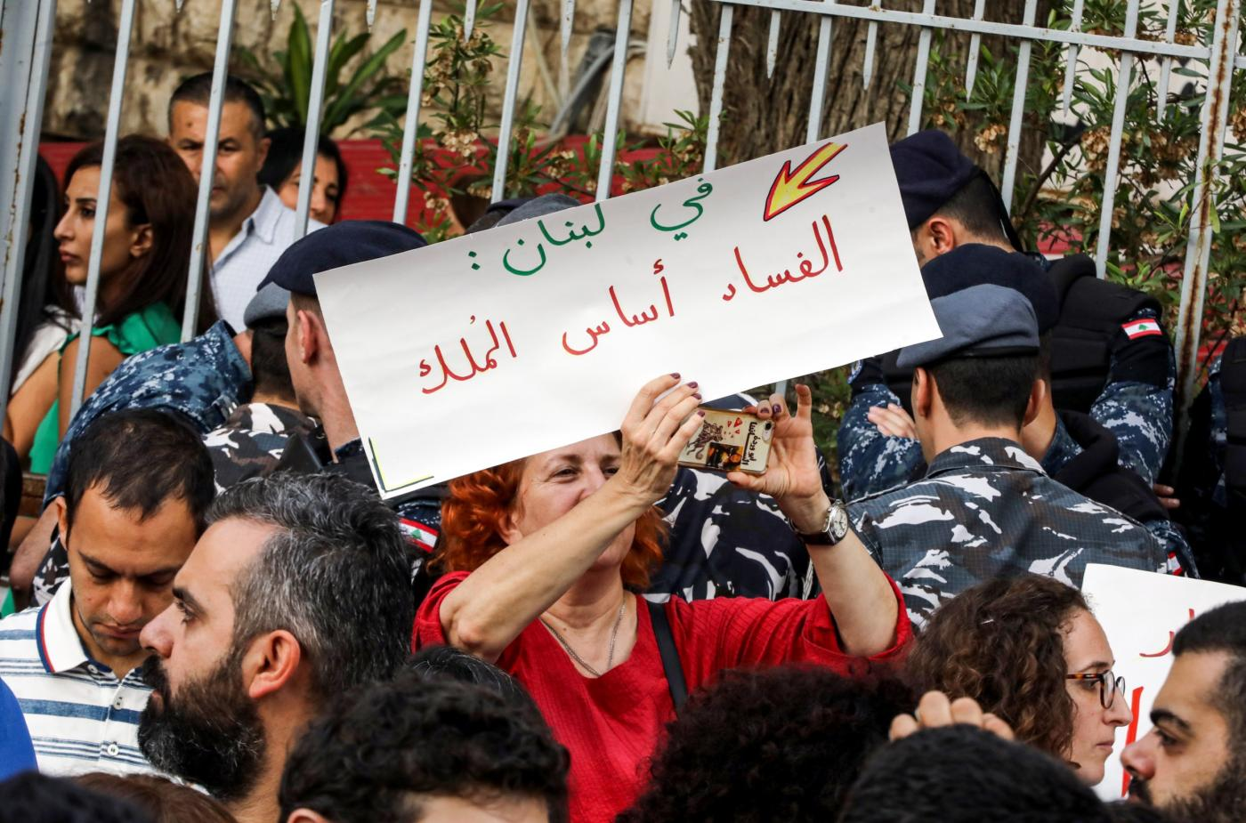 "Protester holding up a sign that reads ""In Lebanon, corruption is the basis of rule,"" outside the Justice Palace in Beirut on 6 November (Middle East Eye via AFP)"