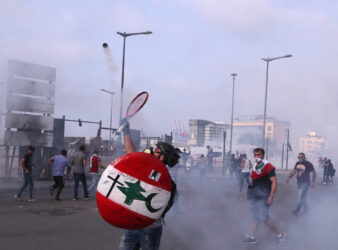 An anti-government protester throws back tear gas at riot policemen with a tennis racket in Beirut, Lebanon on June 6, 2020. (Photo: Al-Jazeera via AP Photo/Bilal Hussein)
