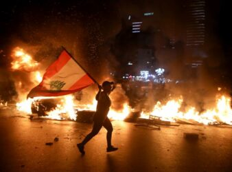 A protester holding the Lebanese flag runs as protesters block the Jounieh Tripoli highway with flaming tires in Beirut late on June 11, 2020. (Photo: CNN)