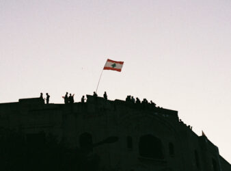 Protesters in Beirut stand on rooftops and wave a Lebanese flag. (Photo: Marylin Chahine)   Protest adapting article