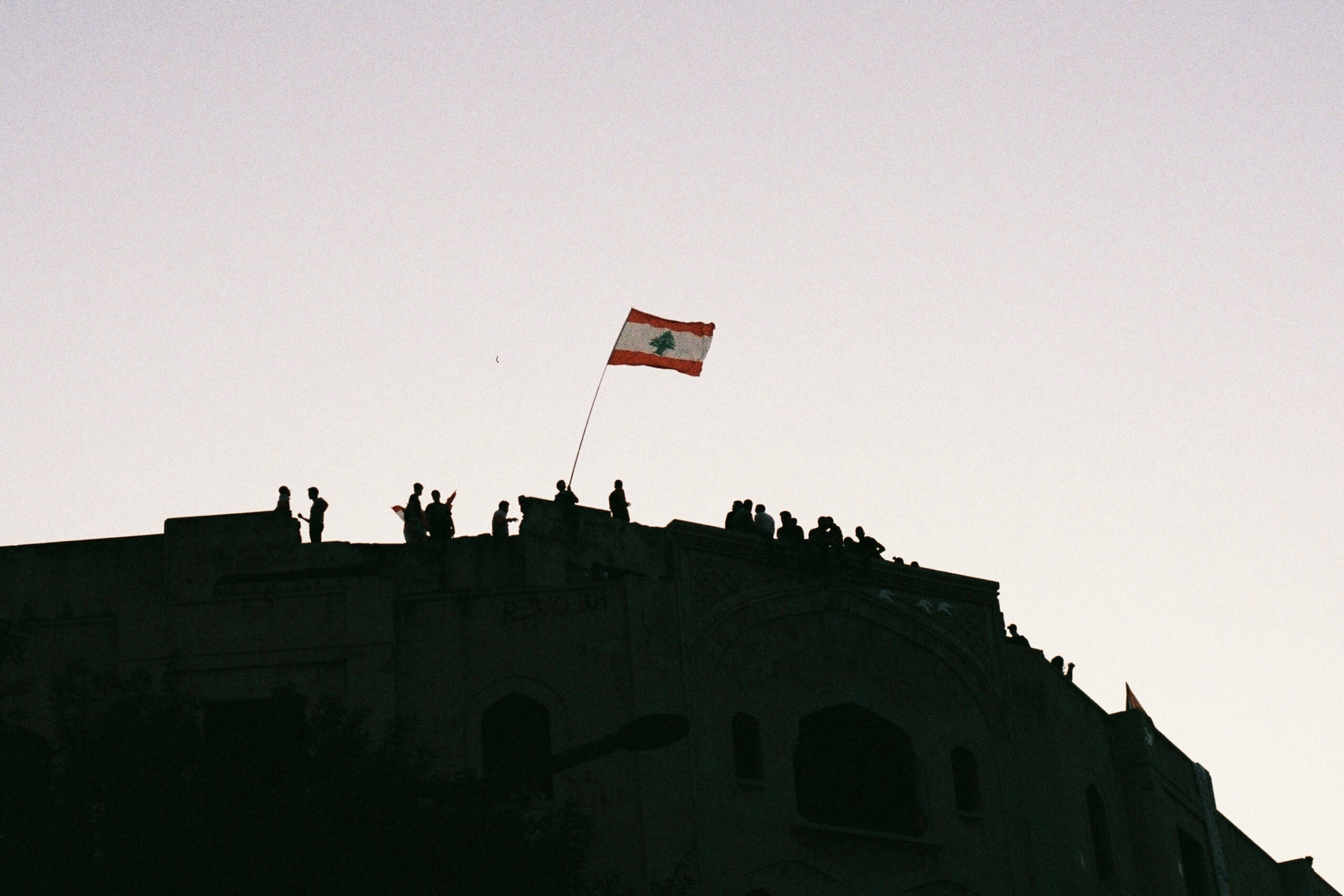 Protesters in Beirut stand on rooftops and wave a Lebanese flag. (Photo: Marylin Chahine) | Protest adapting article