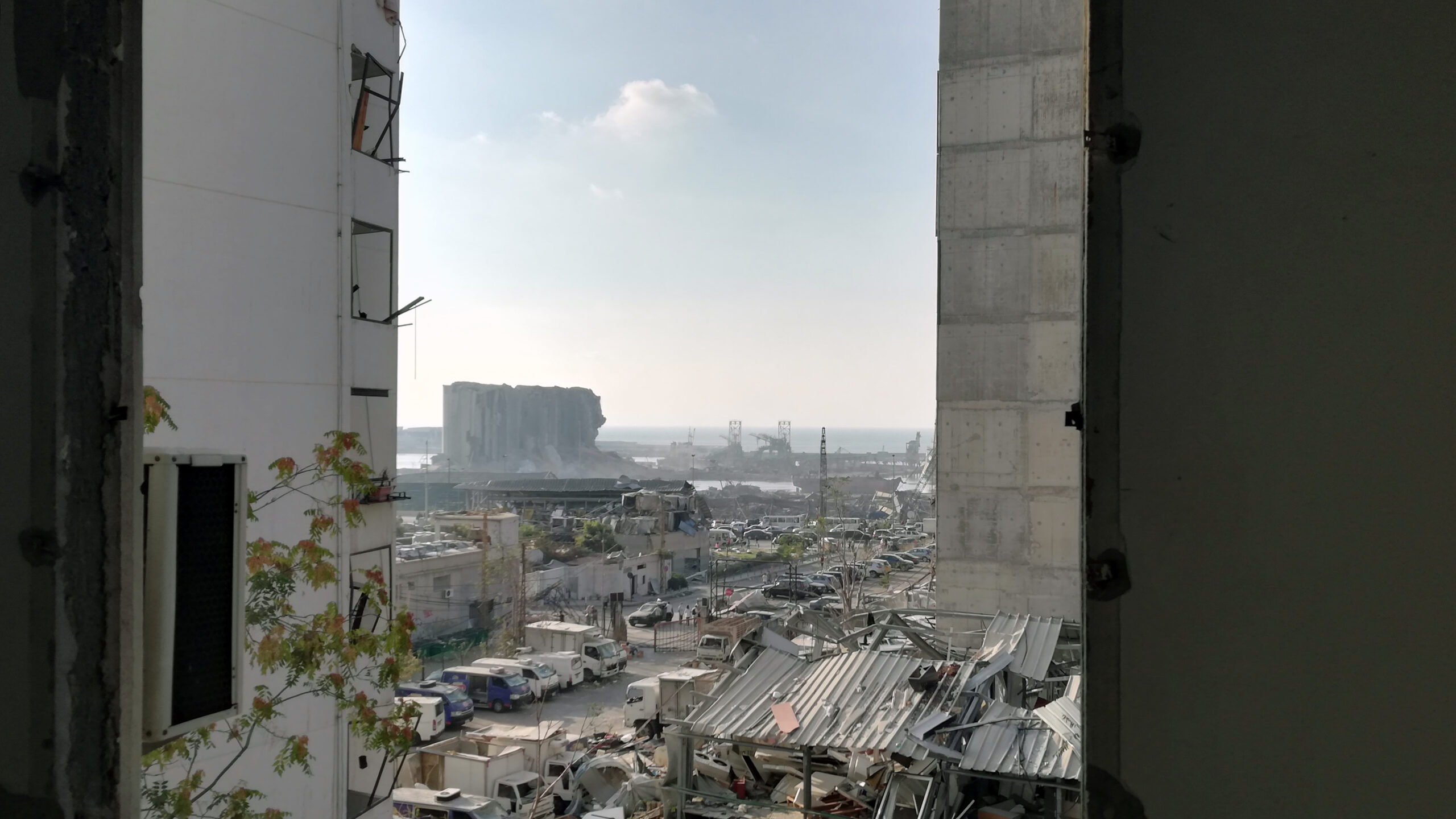 Reconstruction article: The Beirut port as seen through the shattered window of a nearby home after the explosion that decimated the Lebanese capital (Photo: Michael Abounabhan)