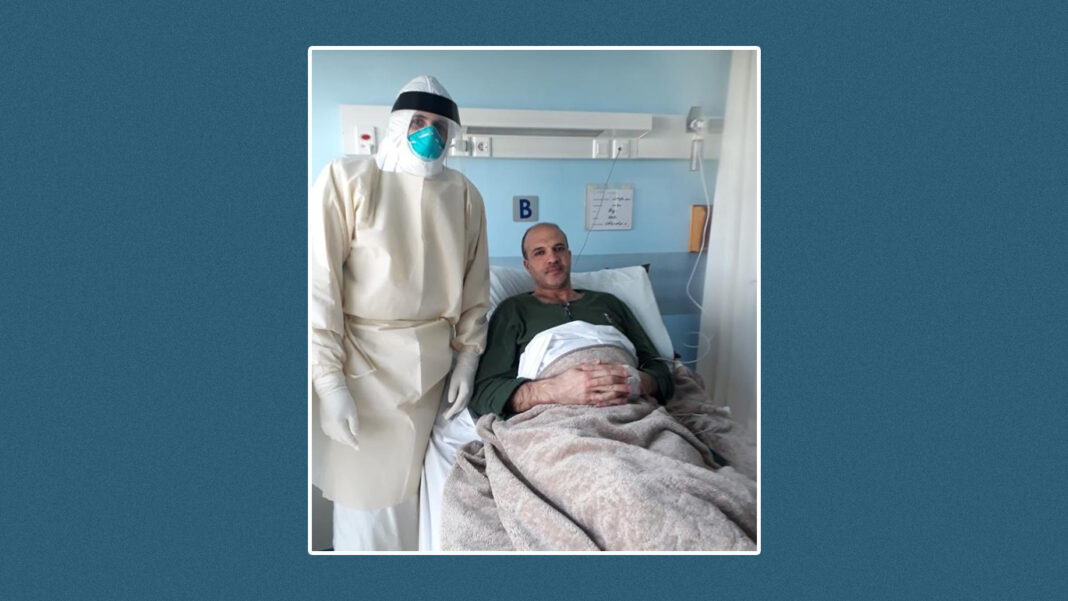 Health minister Hamad Hassan sits in a hospital bed at St. George Hospital while a healthcare worker fully cladded in a hazmat suit stands beside him.