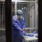 Photo: Medical staff dressed in medical gown and protective gear in a Lebanese prison. Article: WHO calls for inmate vaccination as COVID spreads in Lebanese prisons
