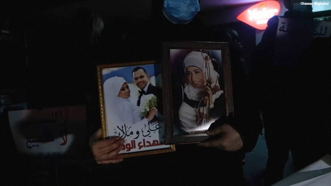 Families of the Beirut blast victims hold up photos of the loved ones they lost in the blast at a protest following the removal of Judge Fadi Sawan from the case. (Photo: Ghassan Mogharbel)