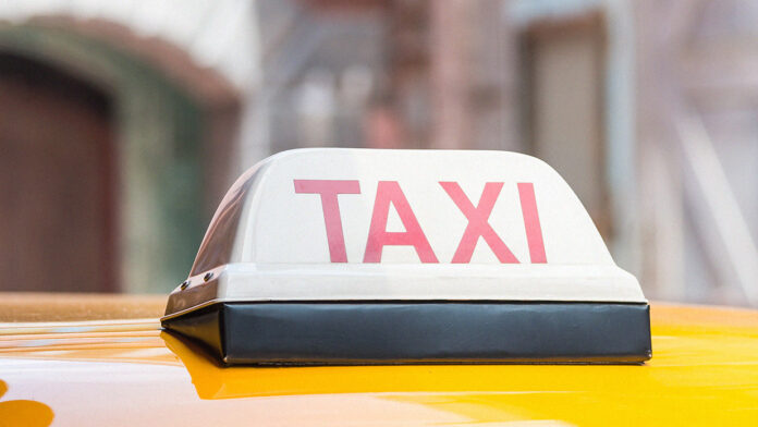 Service taxi article in Lebanon. Close up of taxi sign on top of yellow car with a blurred background.
