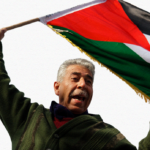 Older man waves a Palestinian flag in Sheikh Jarrah. Photo: flickr.com/photos/libertinus, taken on April 22, 2011.