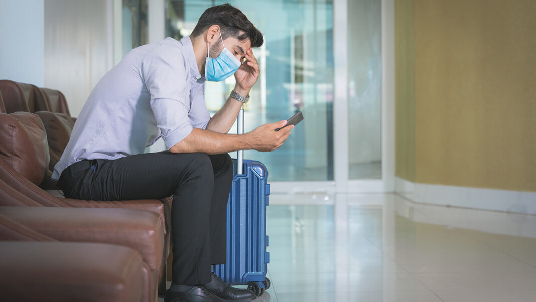 Businessman sits in hotel lobby alone with luggage.