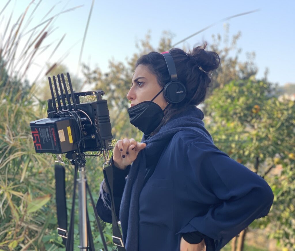 Shot of Mounia Akl on set, wearing a COVID-19 mask and standing behind a camera