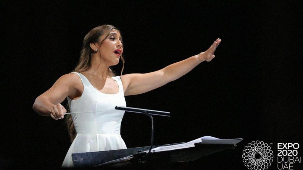 Lebanese conductor Yasmina Sabbah stands at a podium